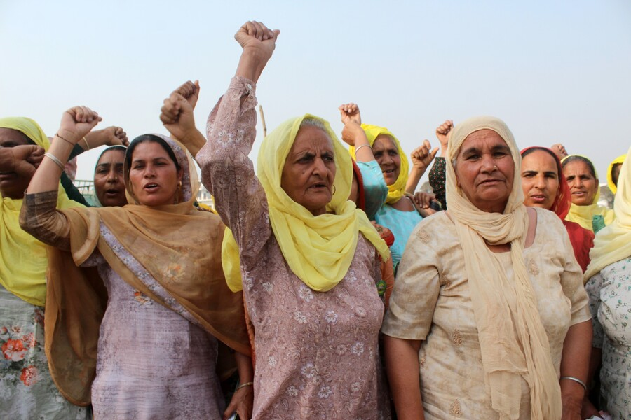 Women farmers shout slogans as they participate in the ongoing farmers protest against new farm reforms on the occasion of International Women's Day at Tikri border (Haryana-Delhi), on the outskirts of New Delhi, India.