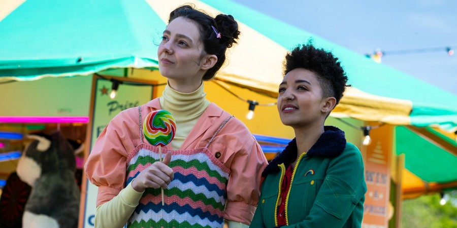 Two teen girls, Lily, a tall white girl with brown hair in buns, and Ola, a short brown girl with short natural hair, stand side by side at a fair.