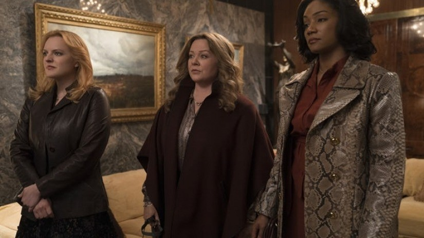 Elisabeth Moss, Melissa McCarthy, and Tiffany Haddish stand in a row with their arms crossed