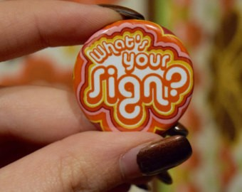 "a woman's hand holding a colorful pin that reads ""What's Your Sign?"""