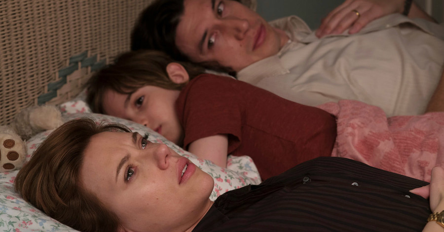 a white couple lays in bed with a small, white child between them in Marriage Story