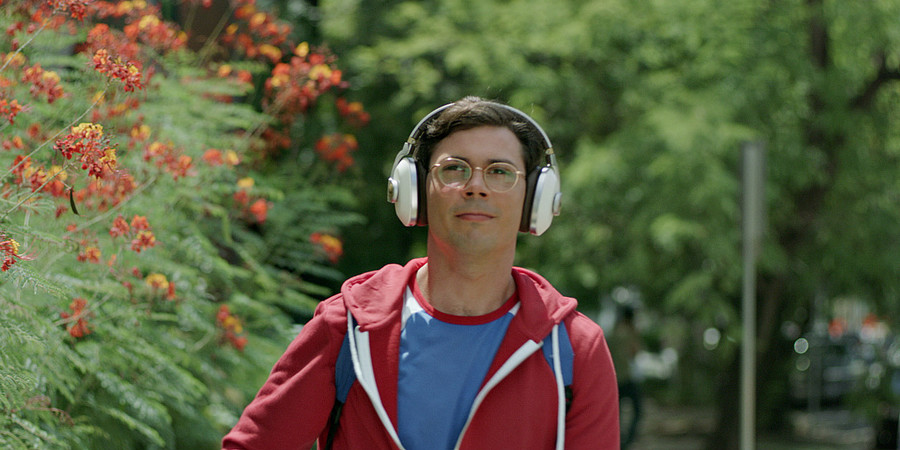 a white man walks down a street with headphones on