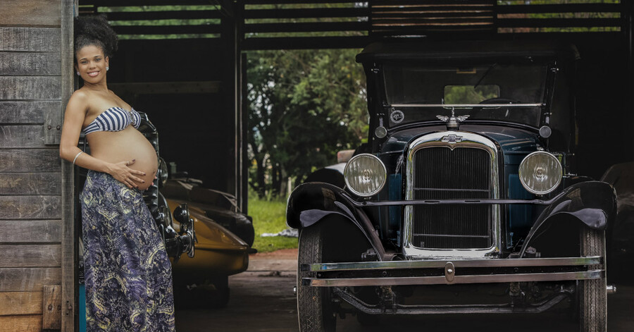 a Black pregnant woman poses in a doorway next to an old school car