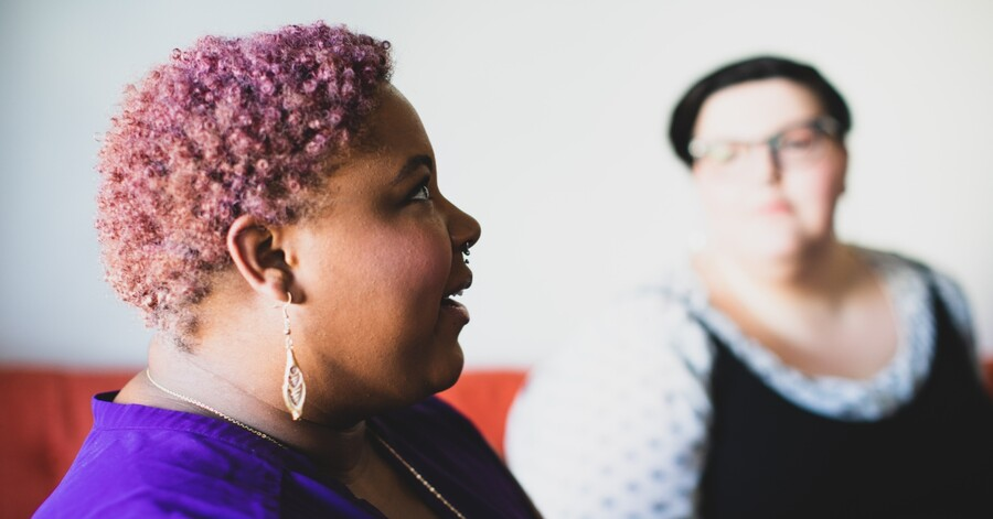 A plus size Black person with cropped pink hair speaks to a friend, who is white and has short dark hair.