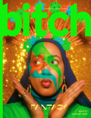 photo of Muslim art and beauty director, Salwa Rahman, in front of a shimmering gold background, wearing a green and orange floral headdress, with decorative 70's-inspired makeup with her hands by her face looking joyful