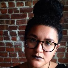 A photo of Devyn Manibo in front of a brick wall. She  has her hair in a bun, neon yellow eyeliner, grey lipstick, and large round eyeglasses. She is making a serious face and had her hair slightly cocked to the side.