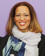 Drew Dixon, a light-skinned Black woman with short, brown hair, smiles at the camera against a purple background