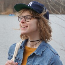 Ana Valens, a white woman with short blond hair and glasses, smiles while wearing a navy blue New York Yankees hat