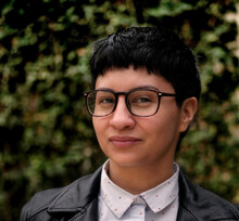Bani Amor, a genderqueer person with short black hair and glasses, wears a black leather jacket as they pose outside