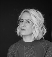 Nina St. Pierre, a white person with short, blond hair, poses in a lace sweater in a black and white photo against a black background
