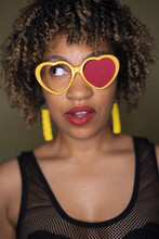 Shanthony Exum, a Black person with short, curly, blond hair, wears yellow heart-shaped glasses
