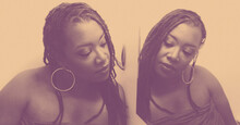 Deesha Philyaw, a Black woman with long, black locs, stares at herself in the mirror, creating a double image