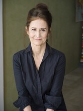 Heidi Boghosian is a white woman with her brown hair pulled back behind her ears