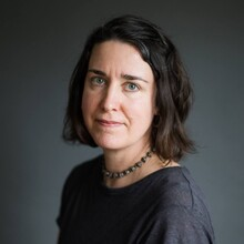 Jennifer Berney, a white woman with short brown hair, is pictured against a gray background wearing a gray shirt