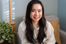 Jennifer Chang, an Asian woman with black hair, smiles brightly at the camera