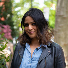 Madhuri Sastry, an Indian woman with shoulder-length brown hair, poses in a black leather jacket and denim button-down shirt