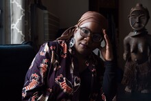 Mariame Kaba, a dark-skinned Black person wearing a brown headwrap and glasses, sits on a turquoise couch