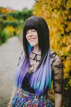 Alaina Leary is a white person with bangs, purple and blue hair, and a colorful dress on. They are smiling and looking down.