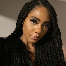 Jaelani Turner-Williams, a Black woman with long, black braids, looks at the camera