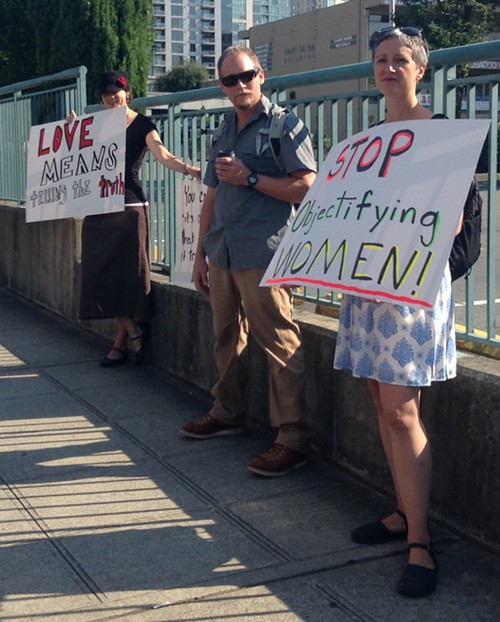 "a woman holds a sign saying ""stop objectifying women"" at a protest outside Mars Hill church"