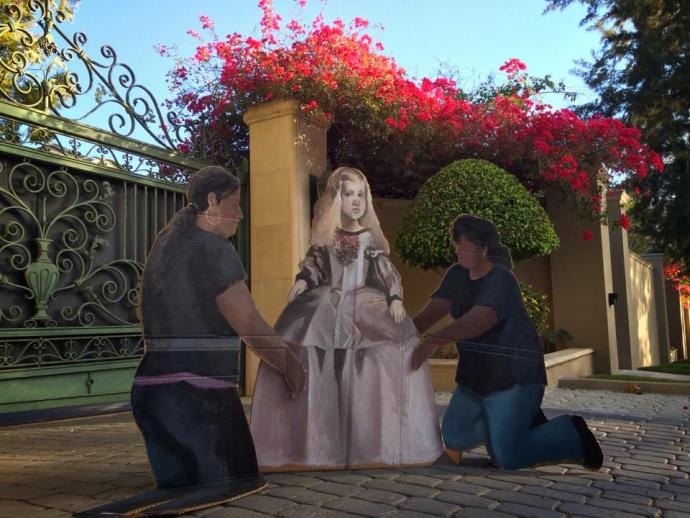 a cardboard cutout of workers fix a fake rich girl's dress in front of a fancy home