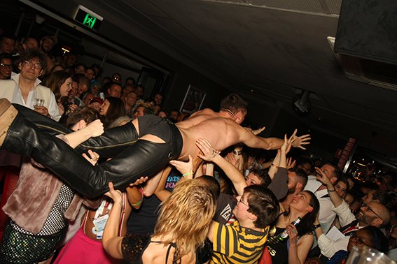 someone crowdsurfing in assless chaps at the no-pants dance party