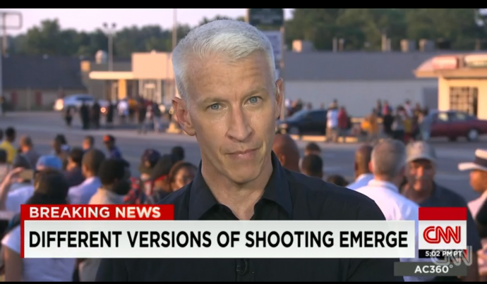 "a still shows anderson cooper over the headline ""different versions of the shooting emerge"""