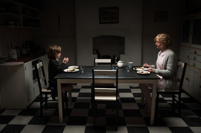 The mother and son sit across from each other at a long table in a dark room
