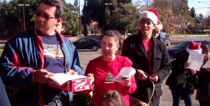 four people wearing santa hats singing outside a clinic