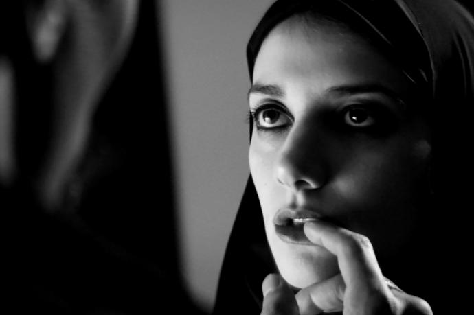 a young girl with vampire teeth wears a chador