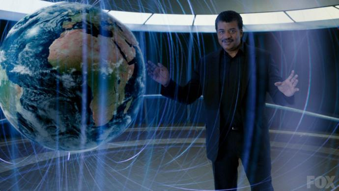 The host of Cosmos, Neil Degrasse Tyson, stands next to an image of the earth surrounded by magnetic fields.