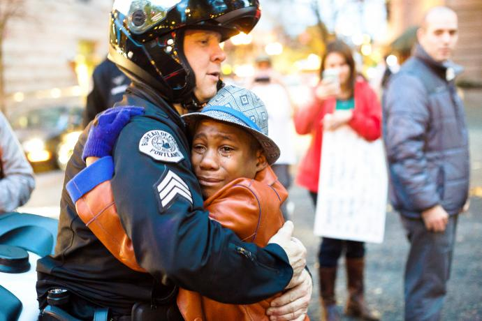 A photo shows 12-year-old Devonte Hart, who is black, crying while hugging a white Portland police officer