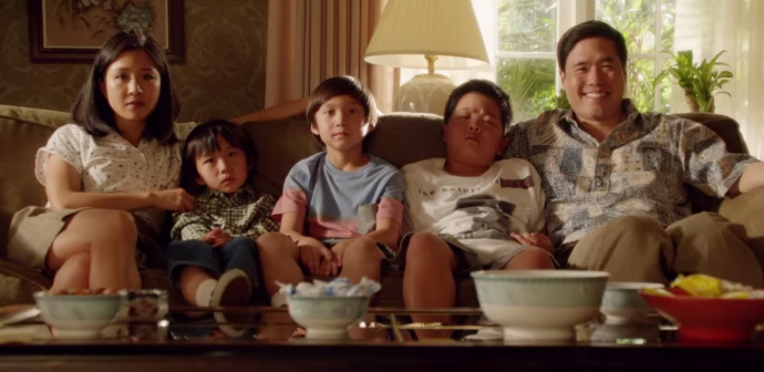 the family in fresh off the boat sits squished on a sofa