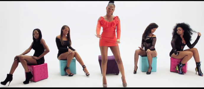 "the rapper lady wears a short orange dress and is surrounded by other women in her video for ""yankin"""
