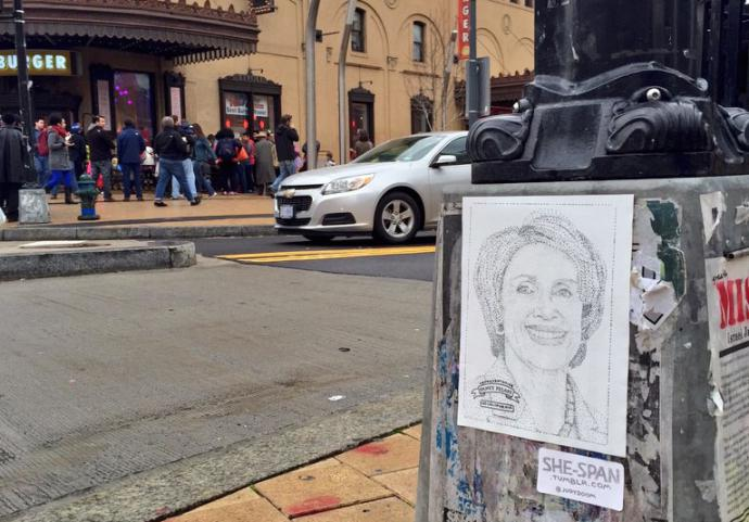 a sticker of nancy pelosi's portrait stuck to a light pole