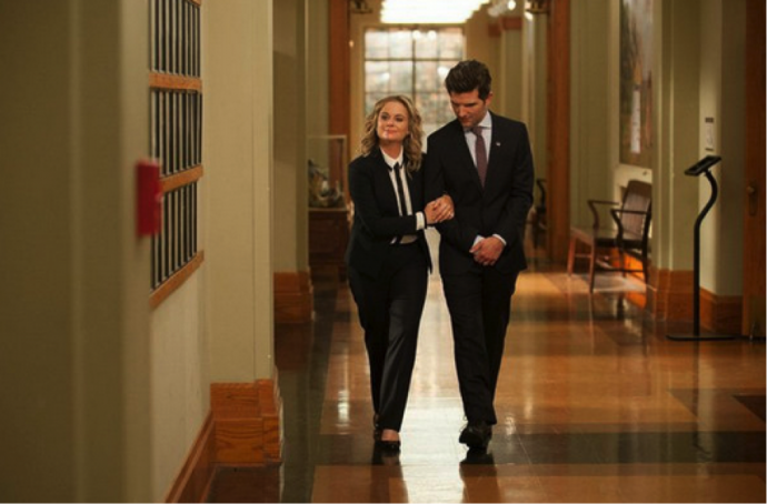 leslie and ben walking down a hall