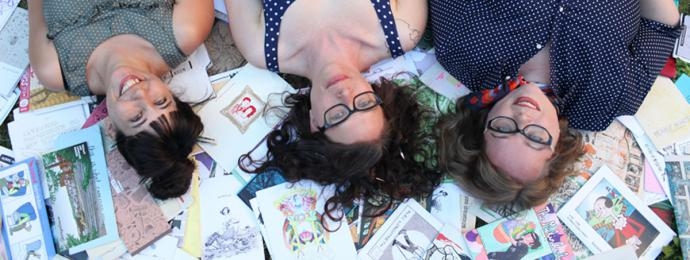 three women lay on a pile of zines