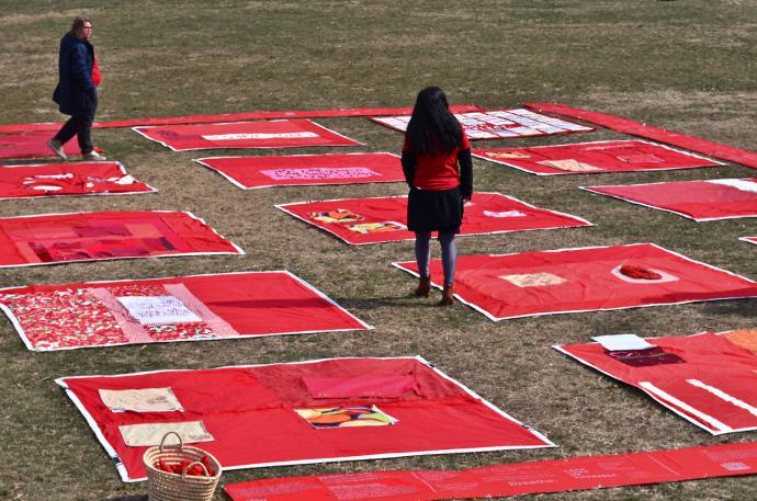 a person walks among the many squares of red forming the monument quilt