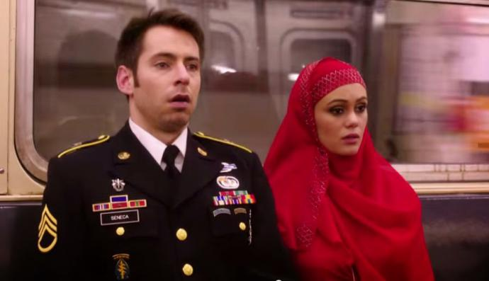 amira, in a bright red hijab, and sam, in his army uniform, on the subway