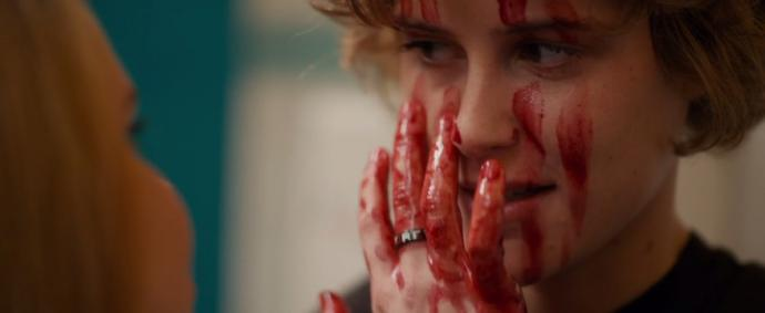 the main character of wetlands joyfully paints her face with blood