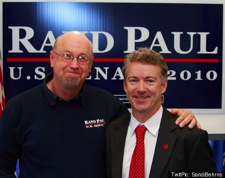 Tim Profitt standing with his arm around Rand Paul in front of a Rand Paul for Senate sign