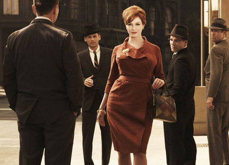 A publicity still from Mad Men, showing Joan Holloway (Christina Hendricks) walking towards the camera while an admiring group of men stares at her.
