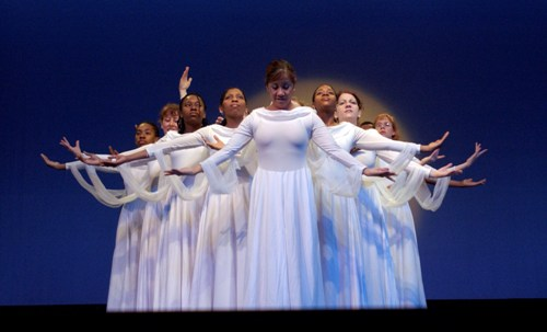A variety of women of many races standing in a v-formation on strage, wearing all white.  They're about to perform as part of Gallaudet University's deaf dance troupe