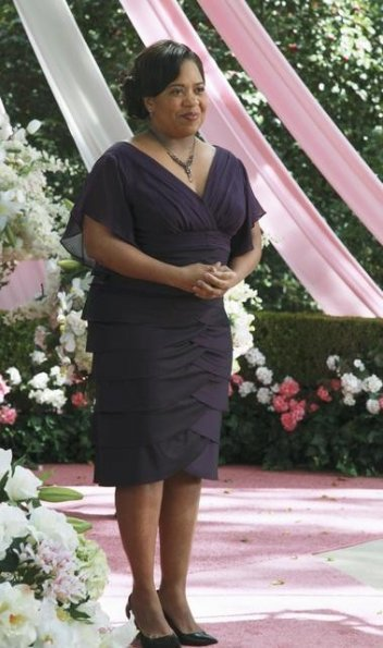 Miranda Bailey (as a member of the wedding party) at the altar in a lovely purple gown, looking excited and nervous.