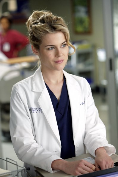 Lucy, a tall blonde woman with elaborately coiffed hair, stands at a counter in her white coat