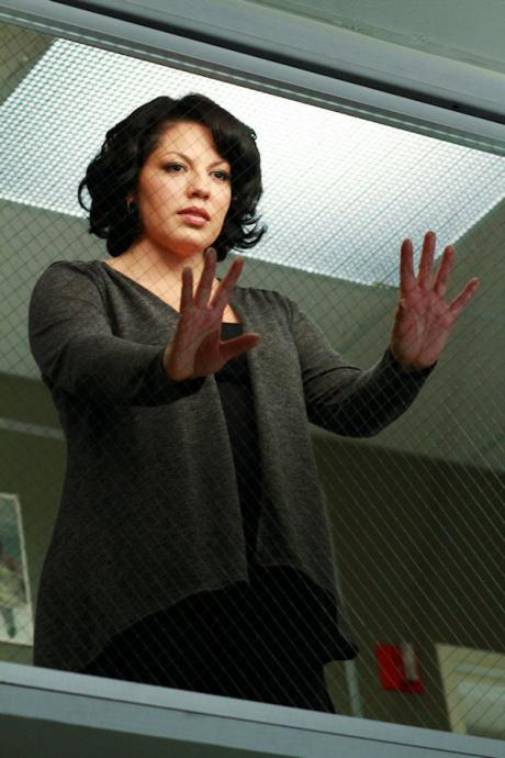 Callie stands in the surgical observation room, hands to the glass
