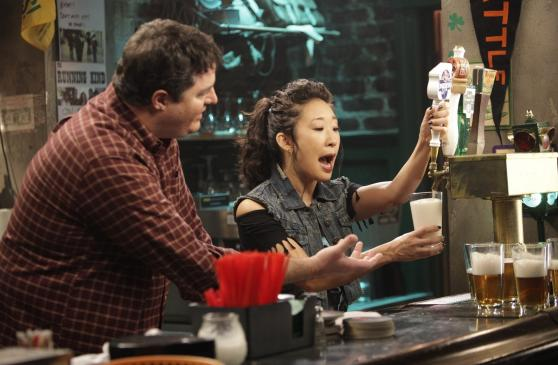 Dr. Yang behind a bar, pulling a pint. Joe the bartender looks on.