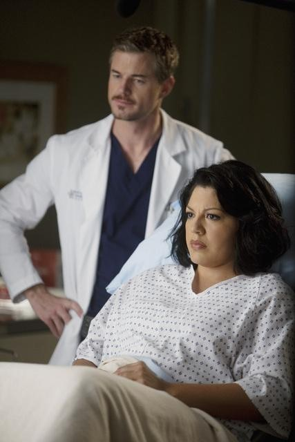 Dr. Torres sitting on an exam table, looking tense, while Dr. Sloane frowns in the background