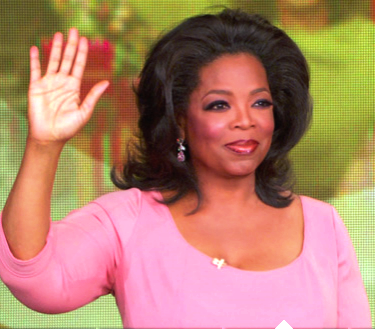 Oprah wears a pink top and a smile. She is waving at her audience, who are off camera.