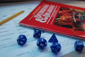 a Dungeons and Dragons game book with several different-shaped die scattered around it